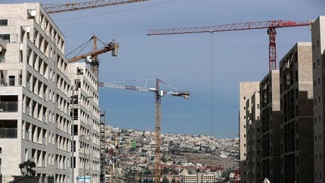Una foto tomada el 17 de enero de 2017 muestra nuevos apartamentos en construcción en el asentamiento israelí de Har Homa, situado en Jerusalén oriental, y una vista del vecindario árabe de Umm Tuba al fondo.