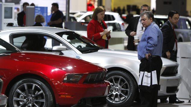 Des consommateurs inspectent des véhicules neufs.Photo Credit: PC / AP/Jim Prisching