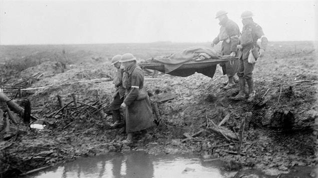 Carrying wounded to an aid post. Just walking through the field was dangerous as a mistep near the slippery mud in the deep water-filled  craters could lead to drowning.