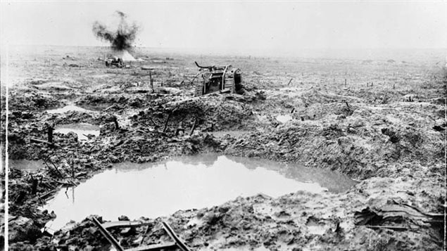 A shell explodes in the blasted muddy landscape near a destroyed tank.