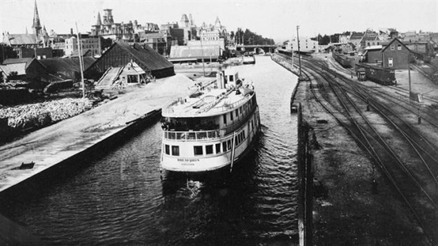 A photograph by Samuel Jarvis, capturing the Rideau Queen steamship travelling north along the canal in the 1890's as seen from the Laurier Ave bridge area. The canal for decades was the site of many industries and cargo and passenger traffic.