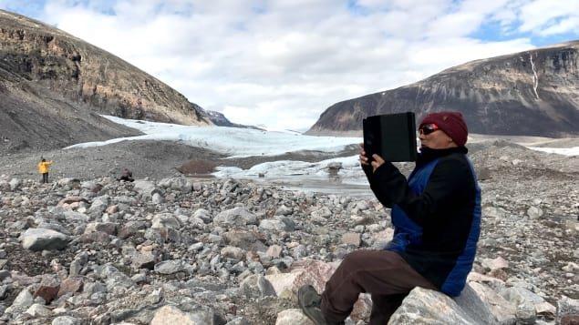 Sam Palituq prend le glacier en photo dans le fjord de Sam Ford, près des montages où il est né. Photo : Radio-Canada/Marie-Laure Josselin