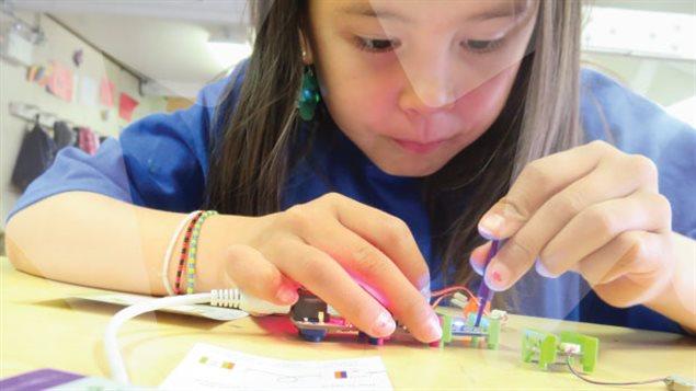 Une fille construit un méchanisme électrique en classe