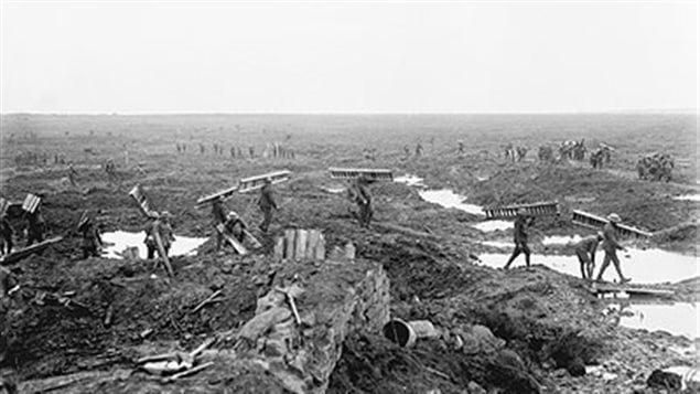 Canadian soldiers carry *trench mats* or *duck boards* across the blasted fields to help movement over the treacherous mud