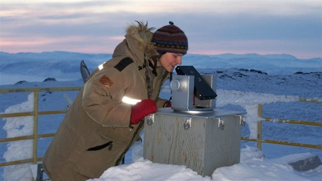 Rebecca Batchelor, a Postdoctoral Fellow at the University of Toronto, checks the alignment of the suntracker on the roof of the Ridge Lab of PEARL, the Polar Environment Atmospheric Research Laboratory. This suntracker follows the sun to direct light into the Fourier transform spectrometer (FTS) in the lab below, where absorption features in the solar spectrum are used to study the quantity and location of a range of trace gases in the atmosphere. (Ashley Harrett/CANDAC)