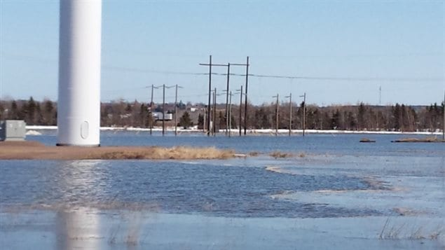 A wind turbine and power poles are surrounded by floodwater on the Tantramar Marsh