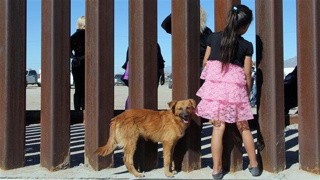Une fille regarde une manifestation anti-mur qui a lieu du côté américaine de la frontière avec le Mexique
