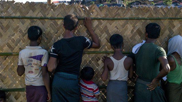 Des enfants musulmans Rohingya du Myanmar regardent à travers le mur en paille qui entoure le camp de refugiés où ils vivent à Balukhali au Bangladesh