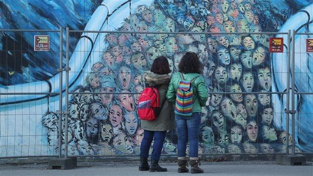 Deux femmes regardent un graffitti dessiné sur l'ancien mur de Berlin