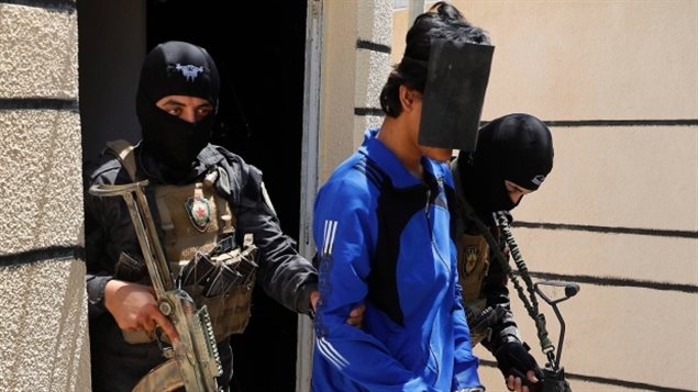 Kurdish soldiers from the Anti-Terrorism Units escort a blindfolded Indonesian man suspected of ISIS membership, at a security centre, in Kobani, Syria in June. Several coalition governments have strongly suggested to anti-Daesh forces that foreign fighters should be killed rather than allow them to return. Canada has a policy of reintegration.