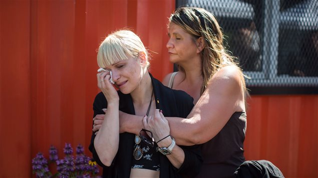A woman is consoled while wiping away tears during a memorial service to remember those who have died in the province as a result of the drug overdose crisis, on International Overdose Awareness Day in the Downtown Eastside of Vancouver, B.C., on Thursday August 31, 2017.