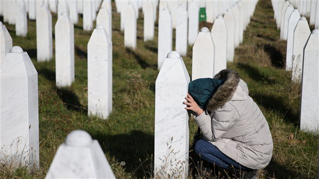 A woman reacts near a grave of her family members in the Memorial centre Potocari near Srebrenica, Bosnia and Herzegovina, after the court proceedings of former Bosnian Serb general Ratko Mladic, November 22, 2017.