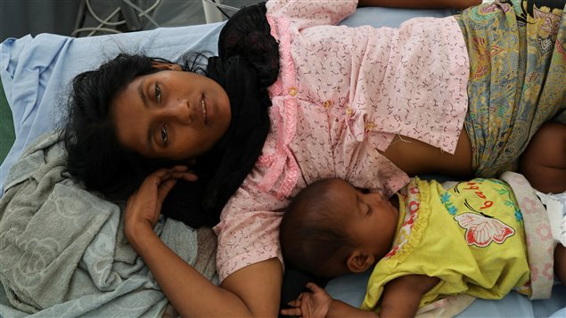 Rohingya refugee Ufaira Begom, 25, who suffers from vomits and dehydration, lies on a hospital bed with her 6-month-old baby Shehena at the Norwegian-Finnish Red Cross field hospital at Kutupalong refugee camp near Cox's Bazar, Bangladesh, November 22, 2017.