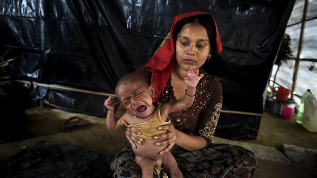 This photograph taken on November 17, 2017 shows a six-month-old Rohingya refugee boy named Mohammad Wahid, who is suffering from malnutrition, sitting on his mothers lap inside a makeshift shelter at Thankhsli camp in the Bangladeshi district of Ukhia.