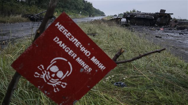 A destroyed military vehicle is seen near a landmine warning sign just outside the eastern Ukrainian town of Slaviansk July 7, 2014.