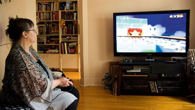 A participant takes part in the study at her home by playing a video game.