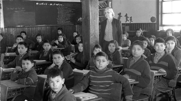 Cree students at their desks in a classroom with their teacher, at All Saints Indian Residential School, Lac La Ronge, Saskatchewan, March 1945.