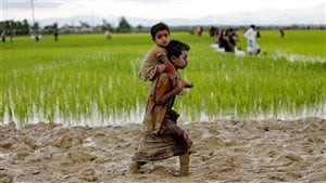 A Rohingya boy carries a child while walking in the mud after crossing the Bangladesh-Myanmar border in Teknaf, Bangladesh, September 1, 2017.