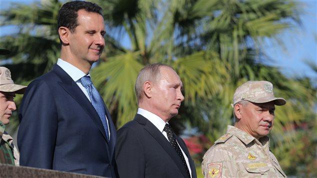 الرئيس الروسي فلاديمير بوتين محاطاً بالرئيس السوري بشّار الأسد عن يمينه وبوزير الدفاع الروسي سيرغي شويغو عن يساره في 11 كانون الأول (ديسمبر) الفائت في قاعدة حميْميم الجوية الروسية في محافظة اللاذقية السورية.