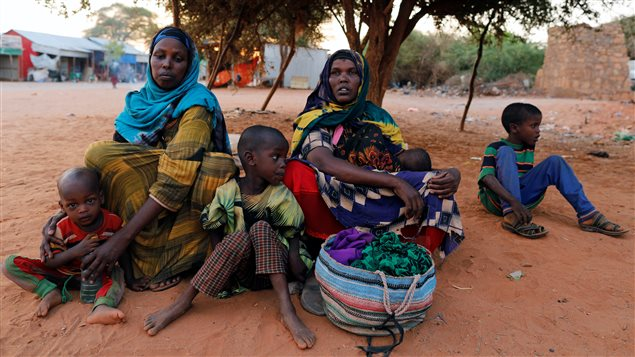 Newly internally displaced women from drought-hit area sit with their children as they wait for help in Dollow.