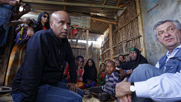 Ahmed Hussen, left, Canada's Minister of Immigration, Refugees & Citizenship who was born and raised in Somalia and immigrated to Canada in 1993, speaks to a Somali refugee family who fled from Kismayo six years ago, and translates the conversation to U.N. refugee chief Filippo Grandi, right, during a visit to Dadaab refugee camp, which currently hosts over 230,000 inhabitants, in northern Kenya Tuesday, Dec. 19, 2017.