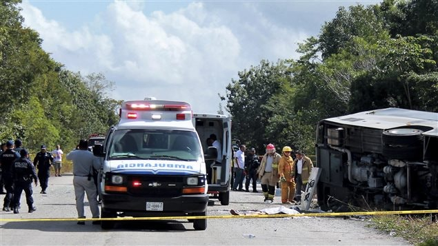 The lifeless body of a passenger lies next to an overturned bus, as ambulances, firefighters and police stand by in Mahahual, Quintana Roo state, Mexico, Tuesday, Dec. 19, 2017. The bus carrying cruise ship passengers to the Mayan ruins at Chacchoben in eastern Mexico flipped over on the highway early Tuesday.