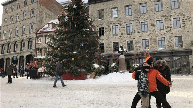 سياح يلتقطون صورة لأنفسهم في الساحة الملكية التي تزينها شجرة ميلاد في مدينة كيبيك.