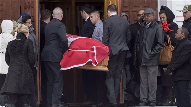 The flag-draped coffin of Lionel Desmond is carried into St. Peter's Church in Tracadie, N.S. on Jan. 11, 2017.