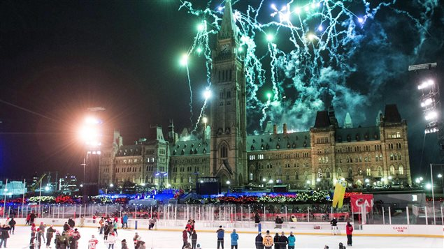 Skaters on the Canada 150 ice rink look on as fireworks explode above Centre Block's Peace Tower during the illumination launch ceremony of Christmas Lights Across Canada on Parliament Hill in Ottawa on Dec. 7,