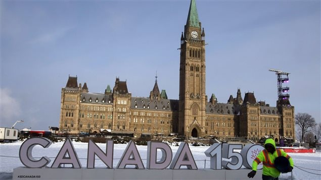 A worker spreads ice melter in front of the Canada 150 sign on Parliament Hill. Heritage Canada was forced to cancel numerous Canada 150 events in Ottawa and elsewhere because of the extreme cold weather conditions currently gripping Canada.