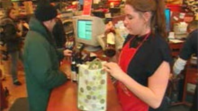 A cashier puts a customer's bottles into a reusable bag at a Montreal liquor store.