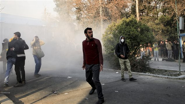 In this photo taken by an individual not employed by the Associated Press and obtained by the AP outside Iran, university students attend a protest inside Tehran University while a smoke grenade is thrown by anti-riot Iranian police, in Tehran, Iran, Saturday, Dec. 30, 2017.
