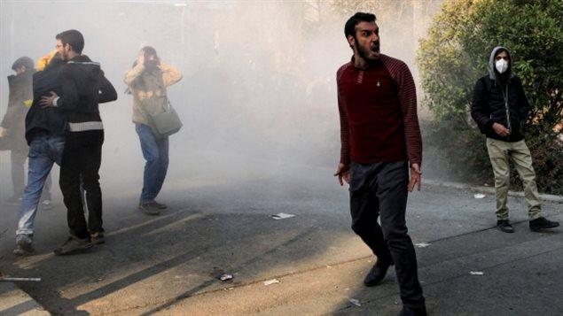 طلاب داخل حرم جامعة طهران يشاركون في الحركة الاحتجاجية يوم السبت الفائت ويبدو الدخان المتصاعد من قنابل دخانية أطلقتها شرطة مكافحة الشغب الإيرانية