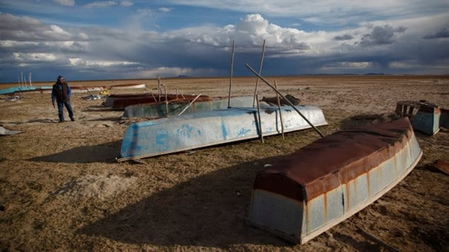 In this Jan. 11, 2016 photo, a fisherman walks along the abandoned boats in the dried up Lake Poopo, on the outskirts of the town of Untavi, Bolivia