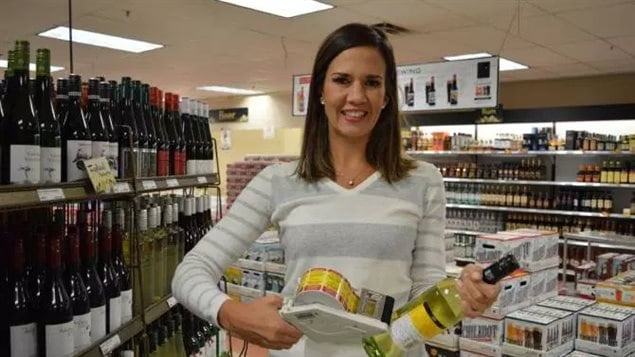 Erin Hobin, one of the leads on the project shown here in 2017 putting labels on wine and spirit bottles in a Whitehorse liquor outlet.