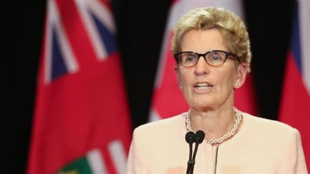 Ontario Premier Kathleen Wynne has increased the minimum wage to $14 this year, and $15 next year. She says moves by business to recoup profits by cutting employee benefits as unfair and the action of bullies.