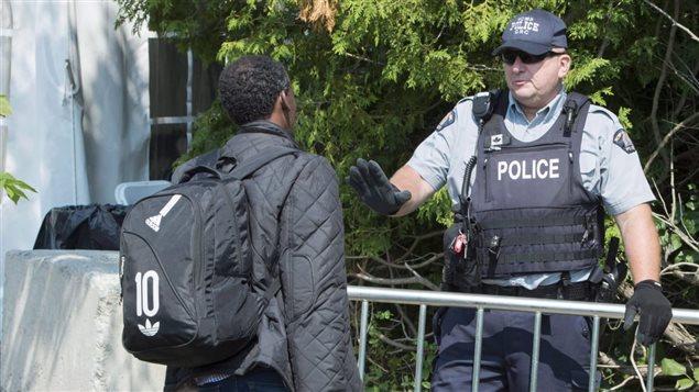 Un demandeur d'asile interrogé par un agent de la GRC à la frontière canado-américaine Photo : La Presse canadienne/Paul Chiasson