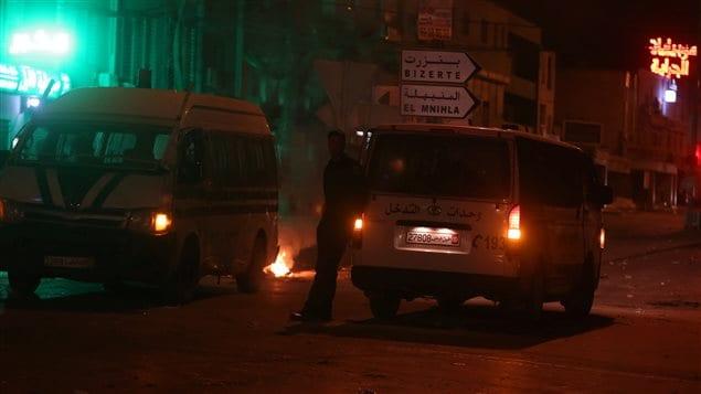 آليتان للشرطة التونسية وإطارات محترقة أشعلها المتظاهرون المحتجون على ارتفاع الضرائب والأسعار الليلة الماضية في تونس العاصمة