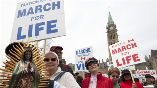 March 2010: Anti-abortion activists march in front of Parliament Hill in Ottawa. Pro-life groups are clearly targetted by the new law as being excluded from grants for summer jobs.