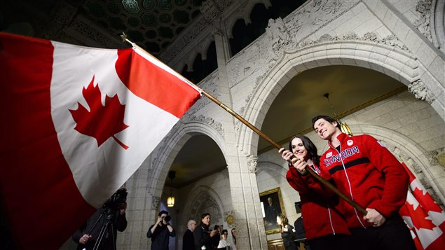 Tessa Virtue and Scott Moir practice waving the flag after the announcement was made on Parliament hill.