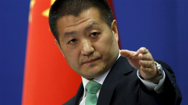 Chinese Foreign Ministry spokesman Lu Kang points out a reporter to receive a question at a regular news conference in Beijing, October 27, 2015.