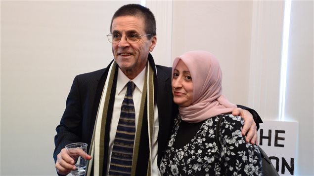 Hassan Diab stands with his wife, Rania Tfaily, as he speaks with reporters in Ottawa on Wednesday.