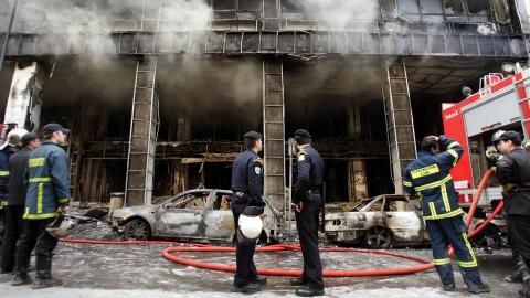 Un bâtiment incendié par les émeutiers à Athènes