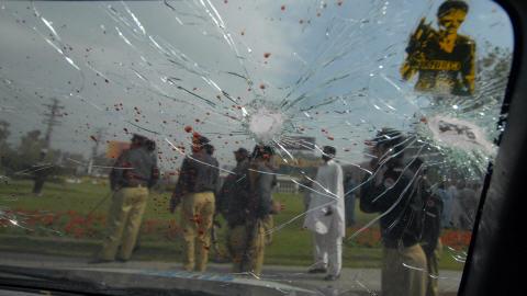 Des policiers pakistanais à l'extérieur d'un camion touché par les assaillants.