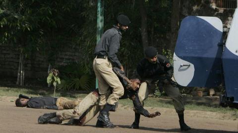Des policiers pakistanais aident un collègue blessé.