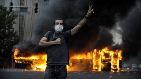 Un autobus brûle derrière un supporter du candidat défait Mir Hossein Mousavi  lors d'une manifestation à la suite du résultat controversé des élections présidentielles.