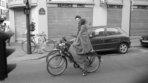 Une femme en burqa se promène à vélo dans les rues de Paris