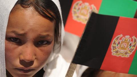 Une jeune Hazara tient un drapeau afghan lors d'un rassemblement politique en faveur de Hamid Karzaï.