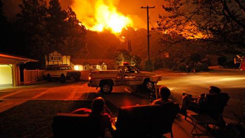 Les pompiers Kevin Klar (à droite) et Eric Tucker (au centre) du comté de Los Angeles sont assis avec Henrik Hairapetian (à gauche), un propriétaire qui n'a pas évacué son domicile, pour tenter de le sauver. Ils sont éclairés par le brasier qui fait rage sur les hauteurs de Los Angeles, samedi.