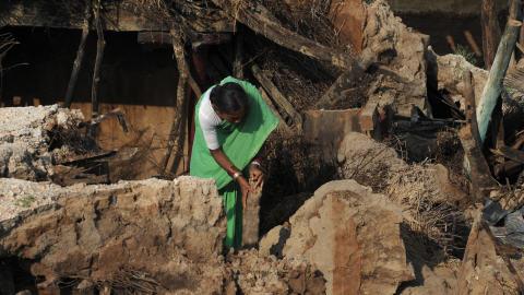 Une femme dans les ruines de sa maison à Burdipadu